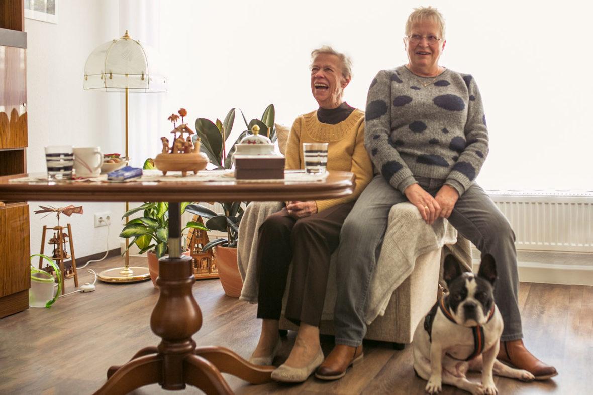 Eine Seniorin und ihre Tochter sitzen in ihrem Zimmer in einer Senioren-WG.