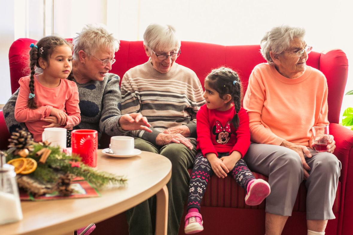 Seniorinnen sitzen mit Kindern auf dem Sofa und unterhalten sich prächtig.