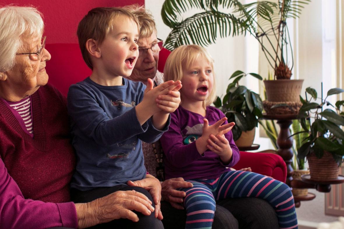 Kinder sitzen bei Seniorinnen auf dem Schoß und zählen.