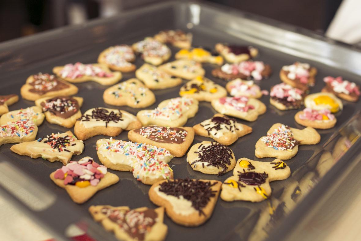 Plätzchen verziert mit Schokostreuseln, rosa, rot, weiß, blauen Streuseln und rosa Zuckerherzen liegen auf einem Backblech.