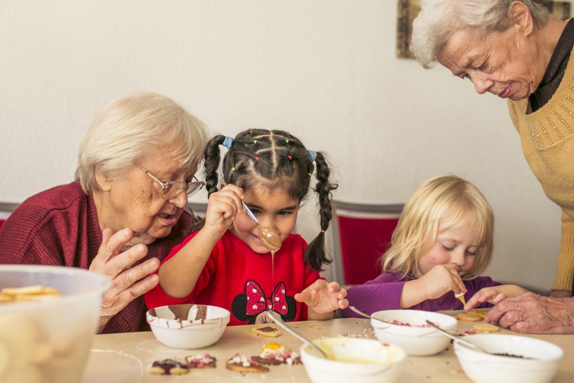 Ein Mädchen mit braunen geflochtenen Zöpfen tropft Schokosoße von einem Löffel auf ein Plätzchen. Eine ältere Dame mit weißen Haaren sitzt neben ihr und sagt etwas.