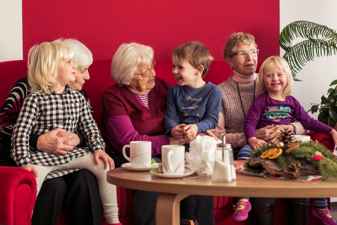 Seniorinnen sitzen mit Kindern auf dem Sofa und Kuscheln