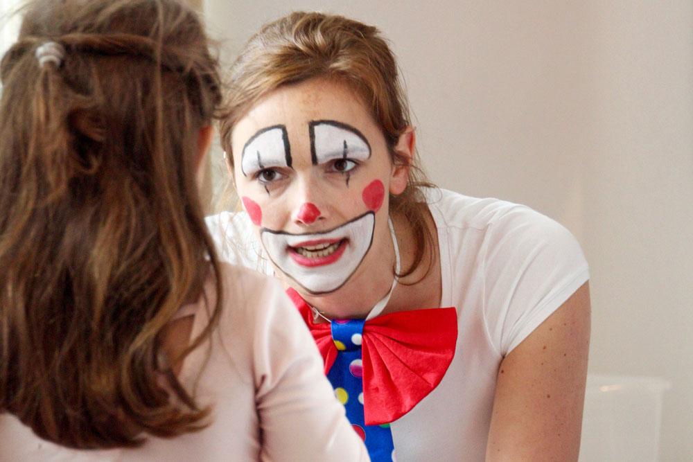 Eine junge Frau ist wie ein Clown geschminkt und spricht mit einem Mädchen.