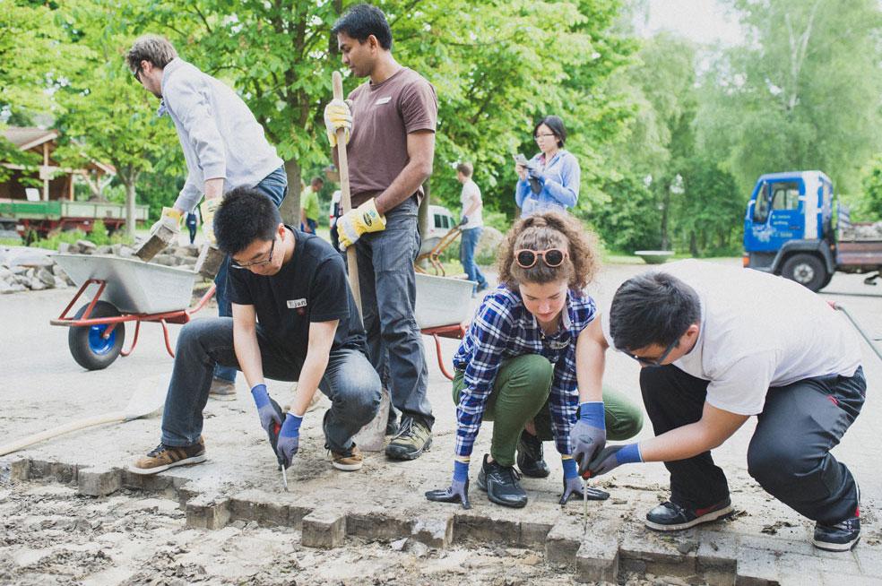 Junge Leute legen Pflastersteine auf einem Weg