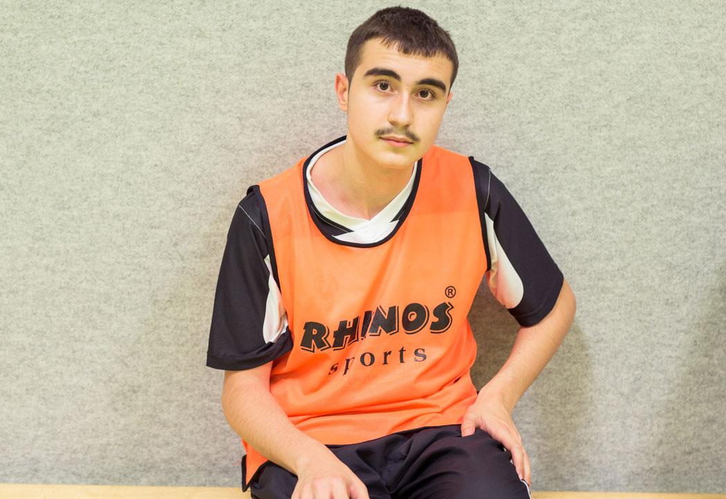 Ein Junge in Sportklamotten sitzt auf einer Bank und blickt ernst in die Kamera.