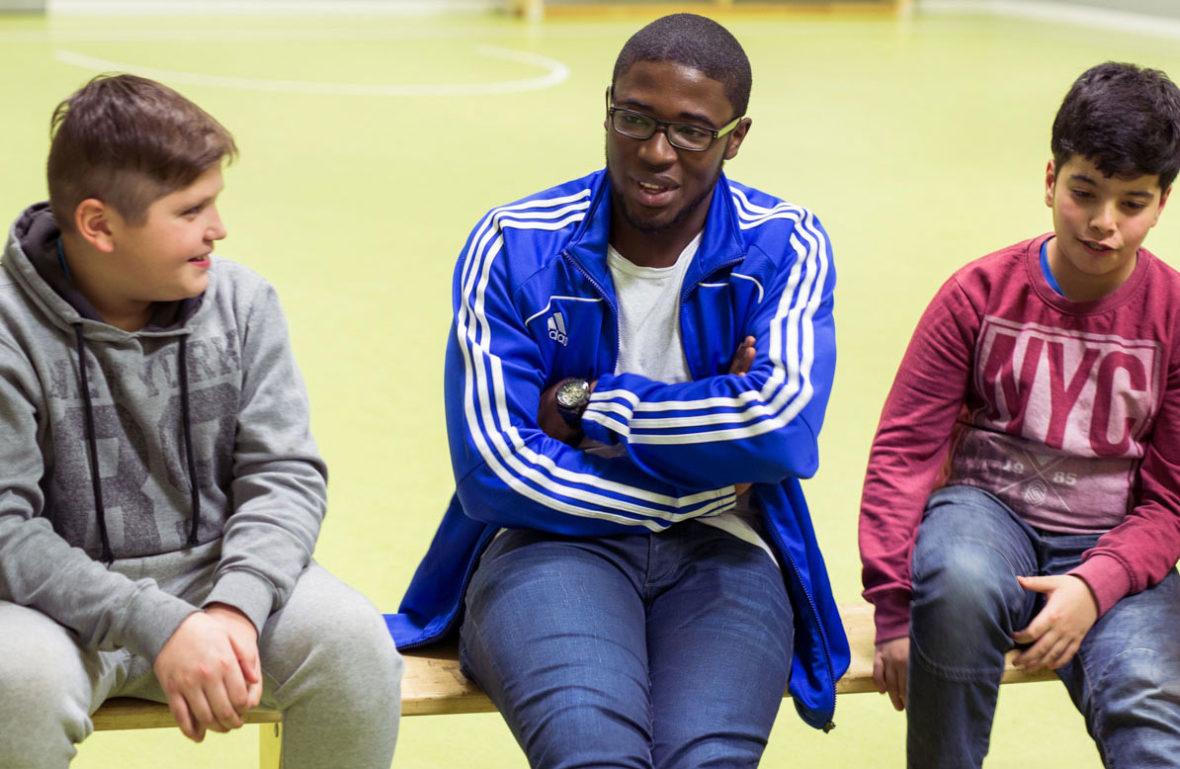 Zwei Jungs sprechen mit dem ehrenamtlichen Trainer Henry Barker