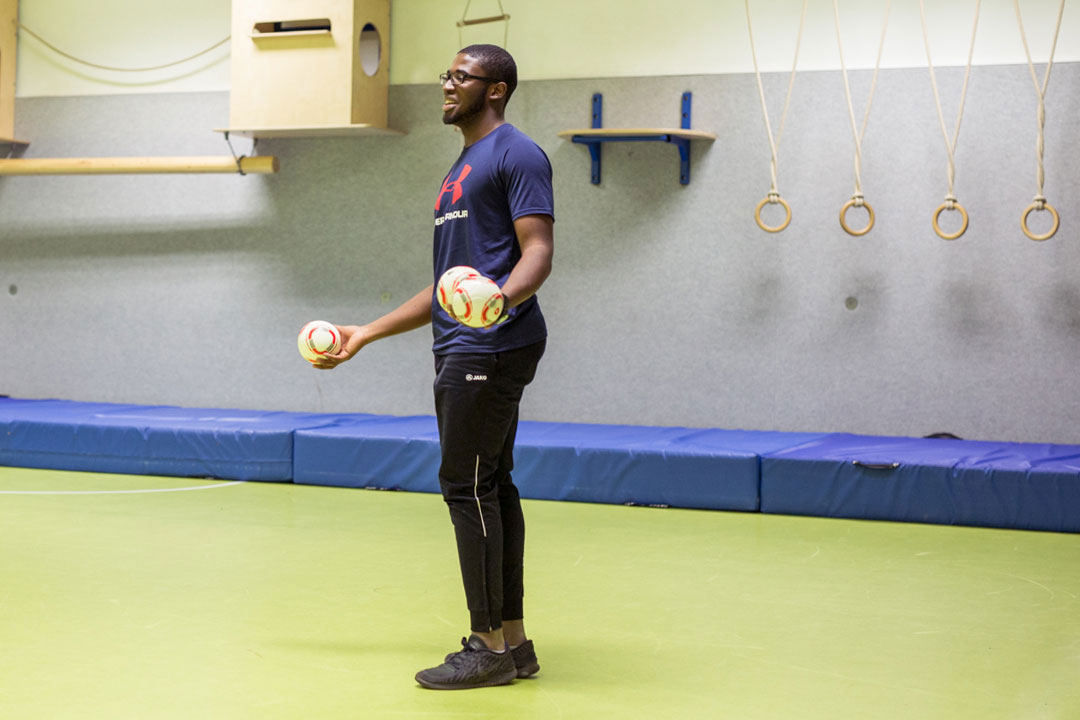 Der Trainer des Coolness-Trainings hält drei kleine Fussbälle in der Hand.