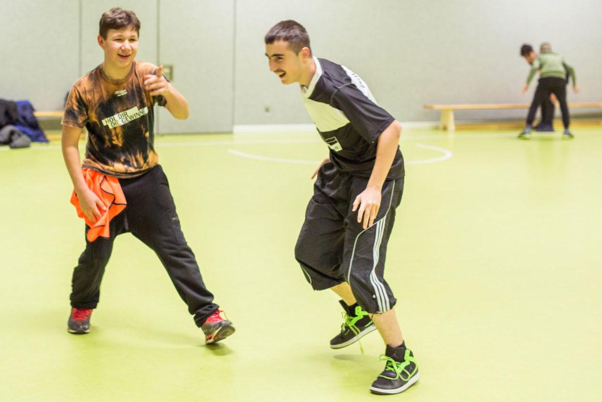 Jungen laufen durch eine Sporthalle und lachen.