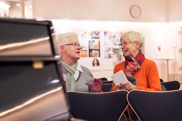 Zwei Damen unterhalten sich über den Vortrag eines Komponisten.