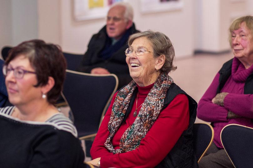 Eine Frau lacht beim Vortrag eines Komponisten.