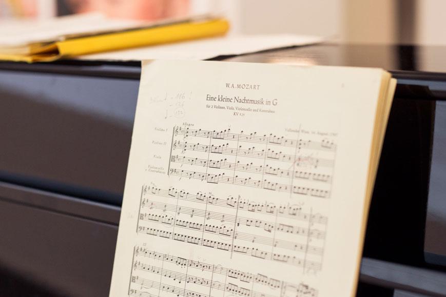 Notenblätter von Mozarts kleiner Nachtmusik in G liegen auf einem Klavier.