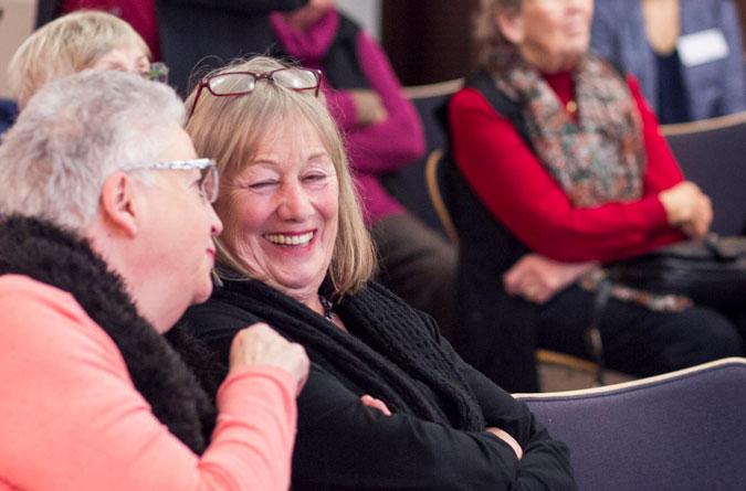 Zwei Damen haben sichtlich Spaß an einem Vortrag.