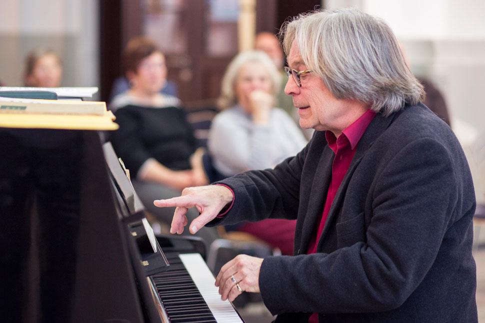 Paulitsch, der Komponist erklärt etwas am Klavier.