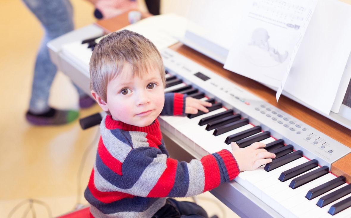 Kleiner Junge sitzt am Klavier.