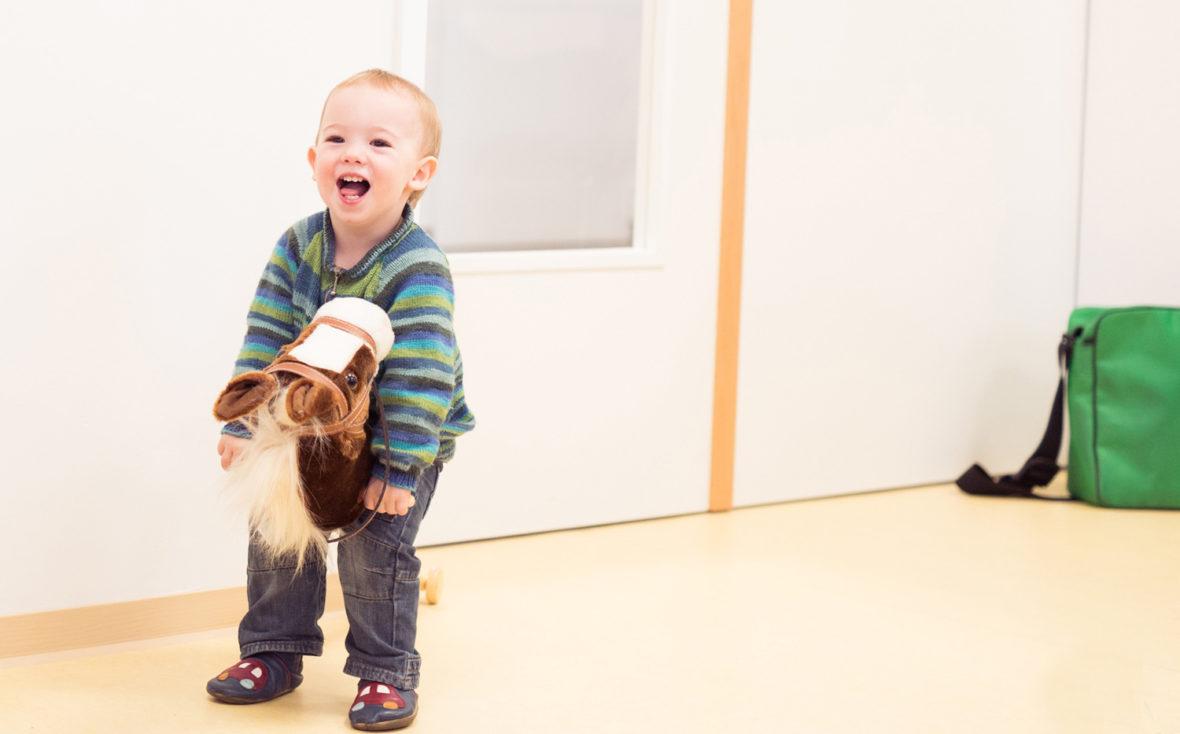 Kleinkind spielt mit Steckenpferd.