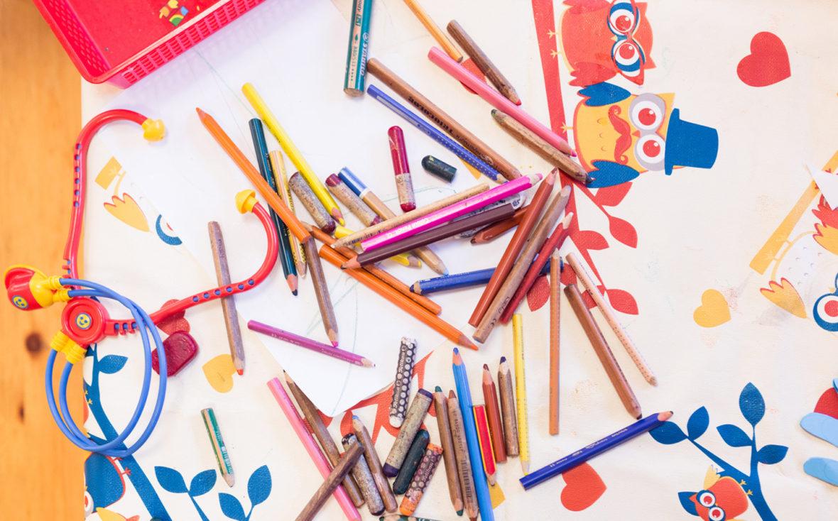 Buntstifte liegen auf dem Tisch.
