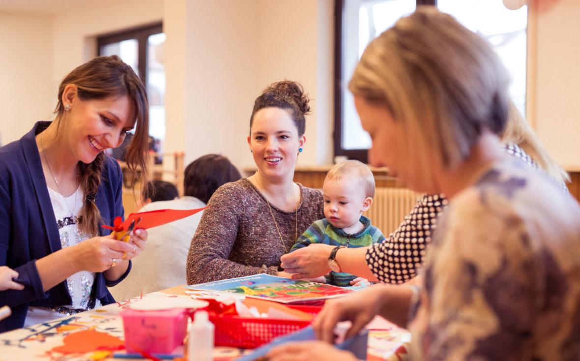 Mehrere Mütter sitzen am Tisch und basteln mit ihren Kindern.