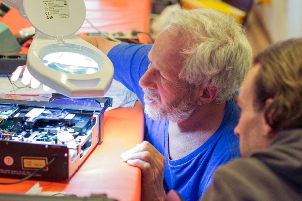 Zwei Helfer untersuchen ein defektes Elektro-Gerät.