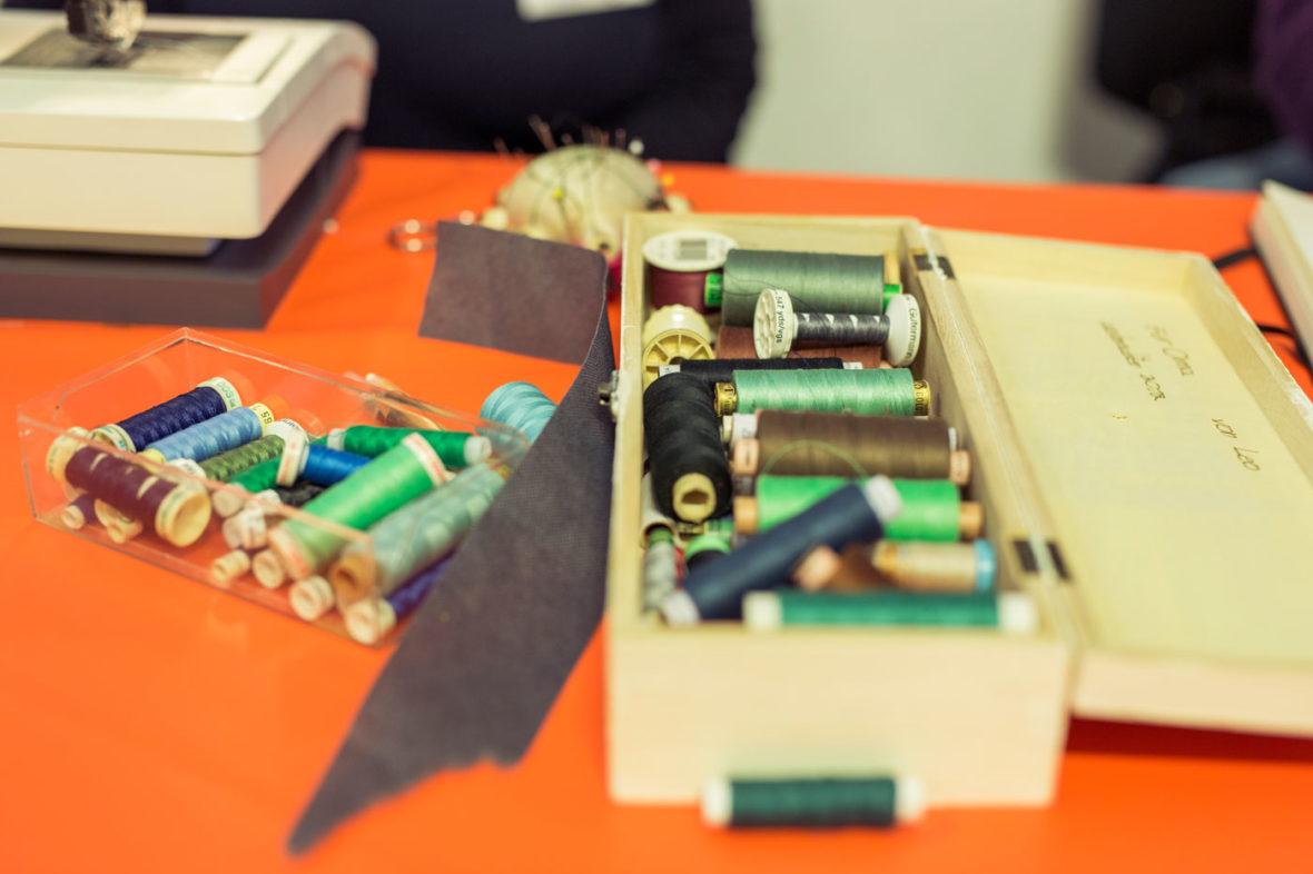 In einer Holzbox liegt Nähmaschinengarn in verschiedenen Farben.