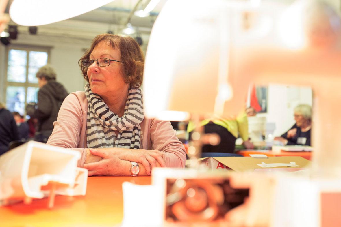 Eine Besucherin des Repair-Cafés sitzt erwartungsvoll am Tisch vor ihrer Nähmaschine: Kann das defekte Gerät wieder repariert werden?