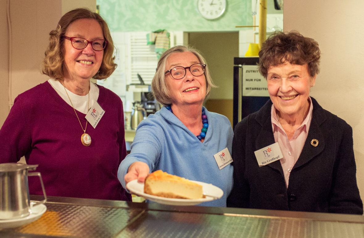 Drei ältere Damen stehen an einem Tresen, eine von ihnen hält einen Kuchen auf einem Teller. Sie lächeln.