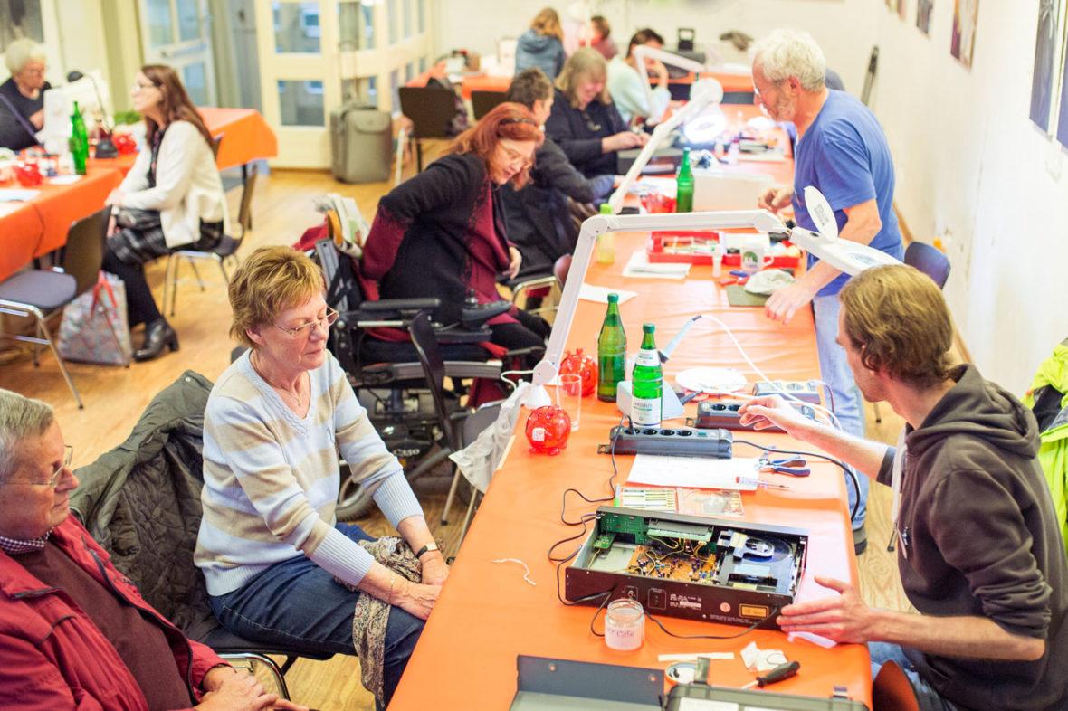 An langen Tischen sitzen ältere und jüngere Leute. Die Helfer sitzen ihnen gegenüber und arbeiten an den defekten Geräten, die die Besucher mitgebracht haben.