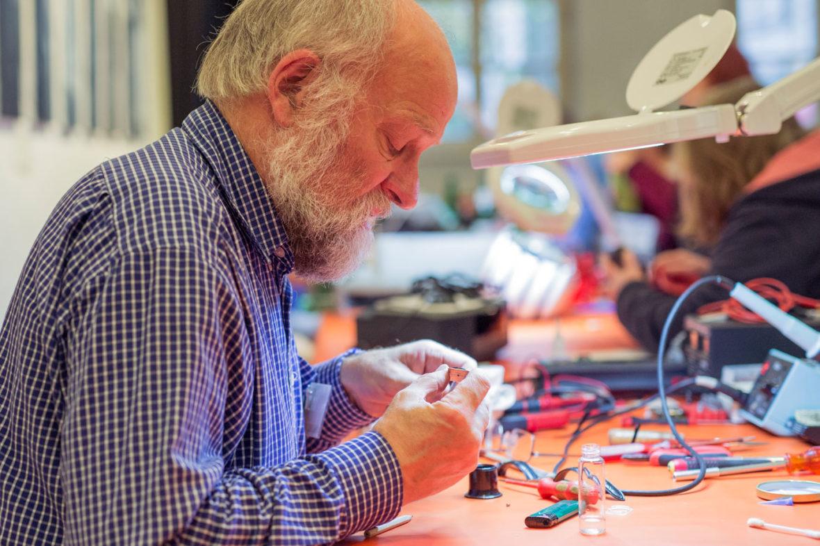 Ein Helfer des Repair-Cafés untersucht ein kleines, elektronsches Ersatzteil.