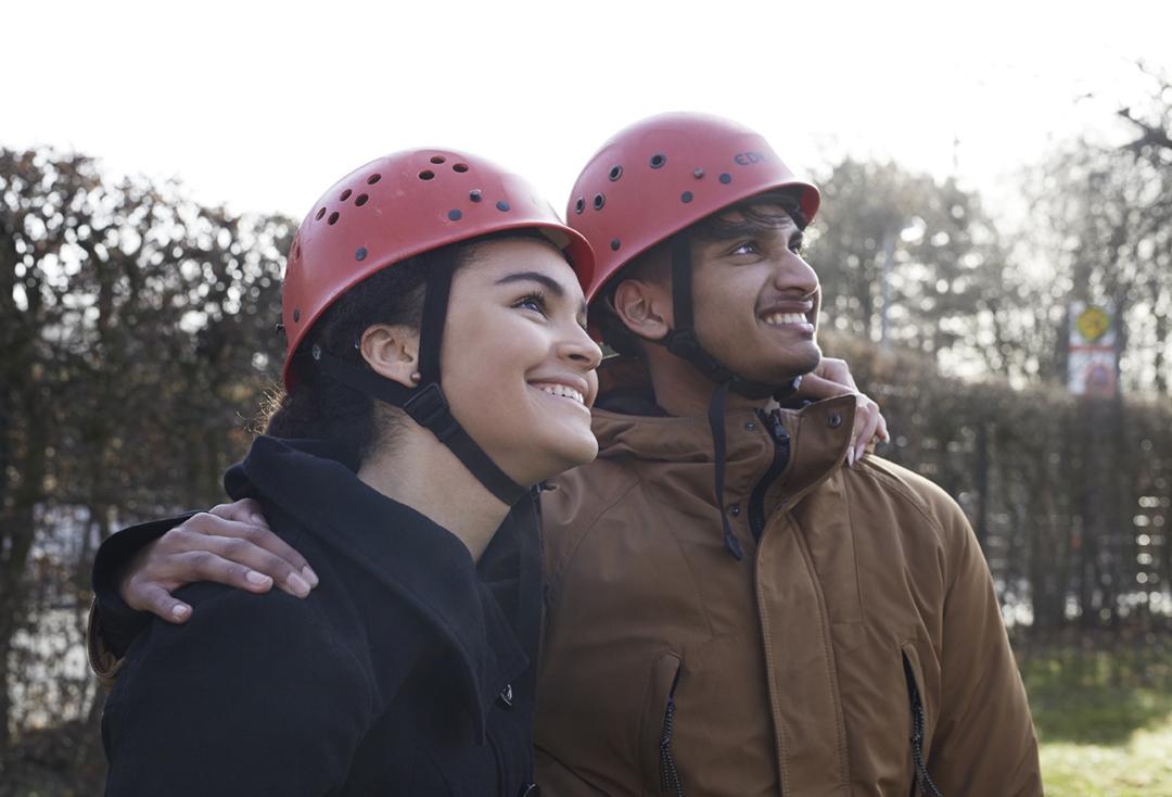 Zwei Jugendliche schauen anderen beim Klettern zu.