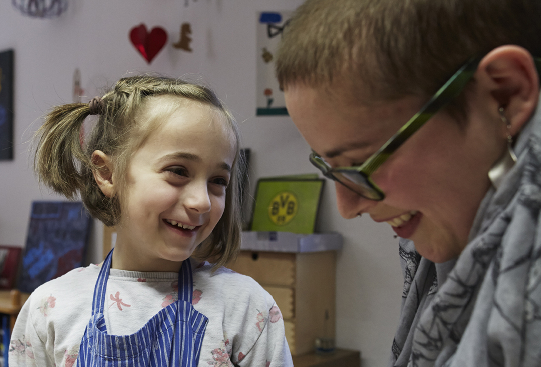 Ein junges Mädchen lacht gemeinsam mit einer Mitarbeiterin der Kinder- und Jugendhilfe St. Mauritz.