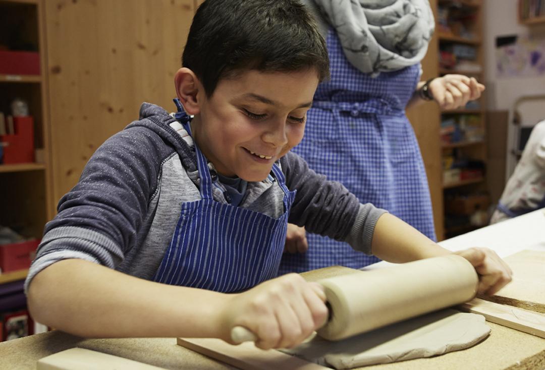 Ein Junge rollt mit einem Nudelholz den Ton aus.