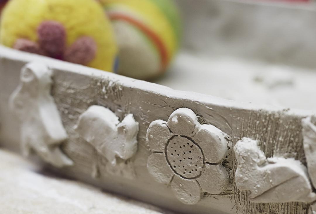 In selbstgetöpferten Tonschalen liegen bunte Eier aus Filz.