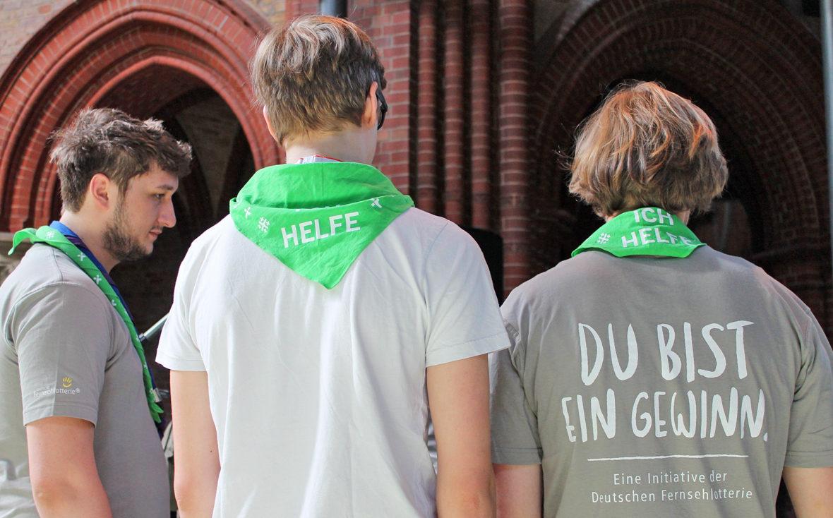 """Die Jungs bei der Besprechung, man sieht den Schriftzug """"Du bist ein Gewinn"""" auf den Shirts"""