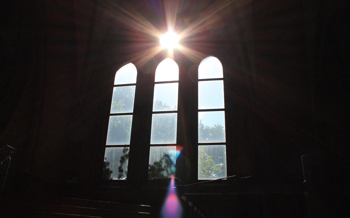 Sonnenlicht bricht durch das Kirchenfenster