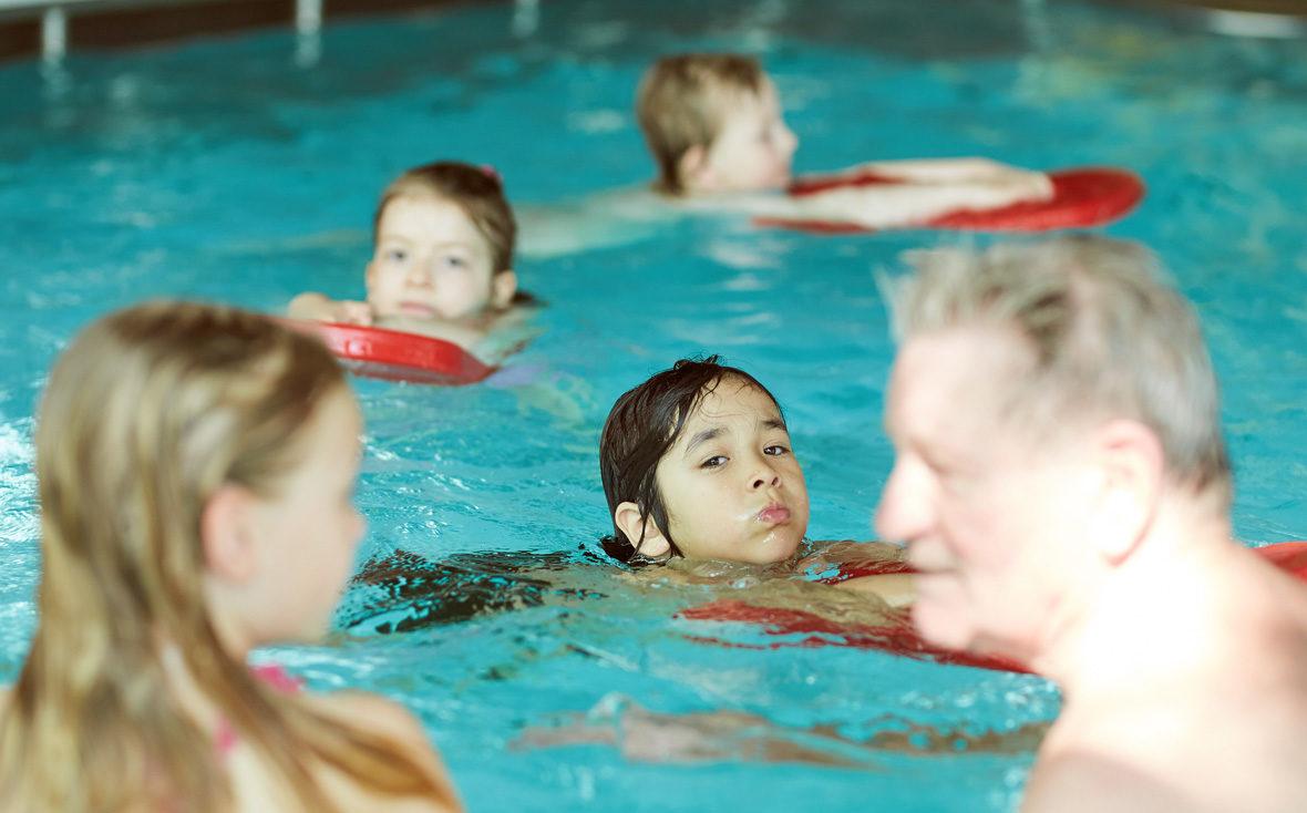 Die Kinder schwimmen mit roten Schwimmbrettern