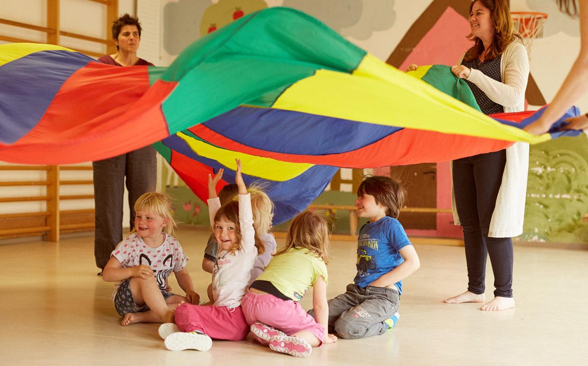 Gruppe Kinder sitzt unter einem bunten Tuch