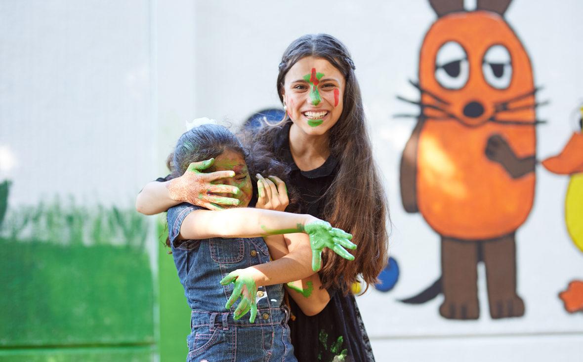 Zwei Mädchen schmieren sich Farbe ins Gesicht.