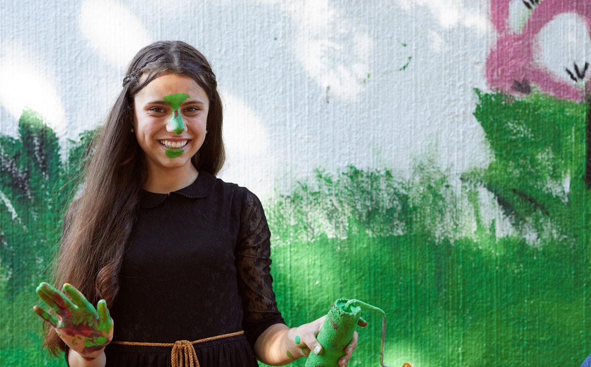 Mädchen mit grüner Farbe im Gesicht.