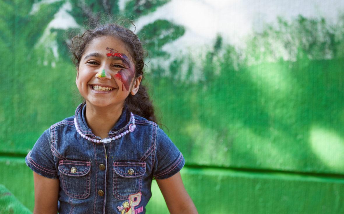 Lachendes Mädchen mit Farbe im Gesicht.