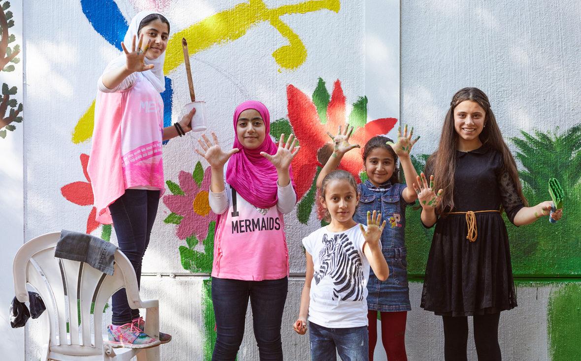 Fünf Mädchen stehen vor der angemalten Wand und zeigen ihre Hände.