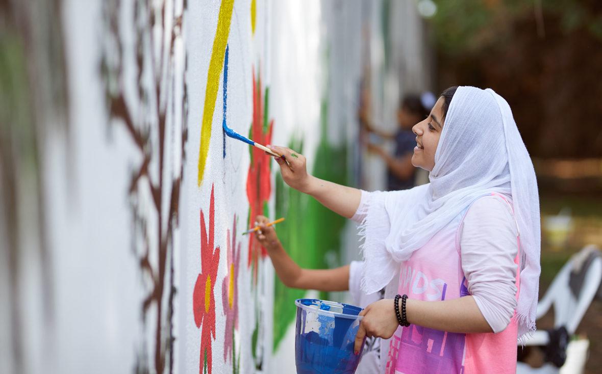 Ein Mädchen mit Farbeimer in der Hand malt an der Wand.