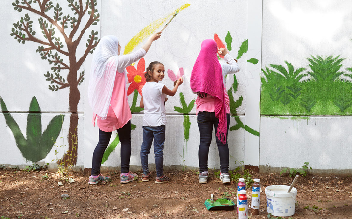 Drei Mädchen malen Blumen an die Wand.