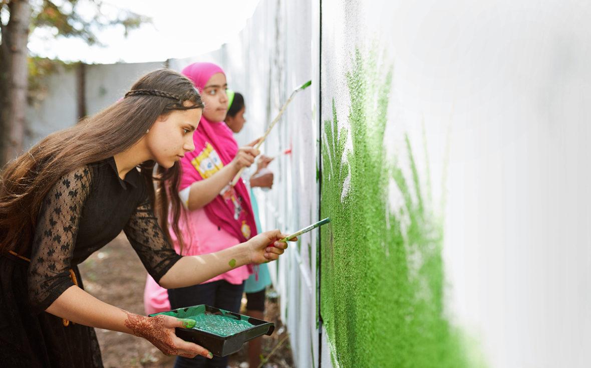 Mädchen malt mit Pinsel die Wand grün.