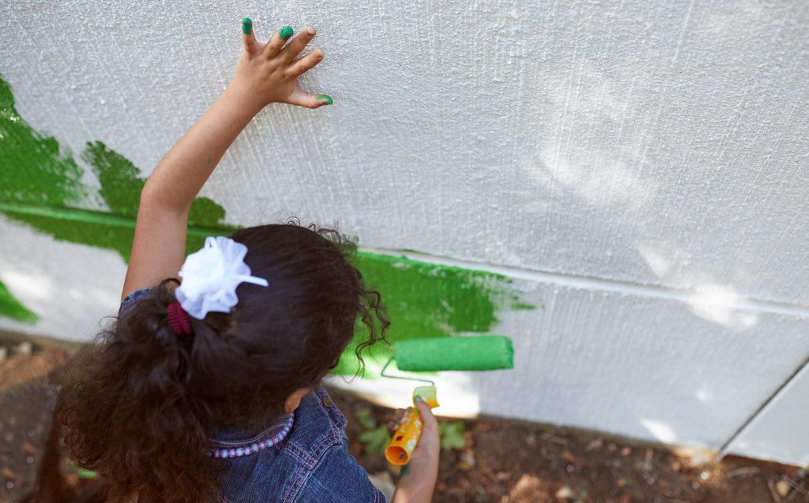 Mädchen malt mit grüner Farbrolle die Wand an.
