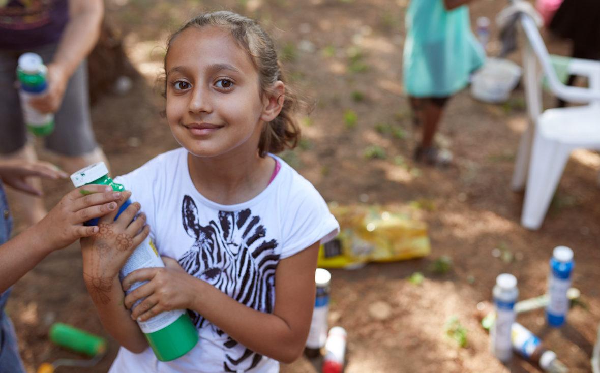 Ein Mädchen hält eine grüne Farbflasche in der Hand.
