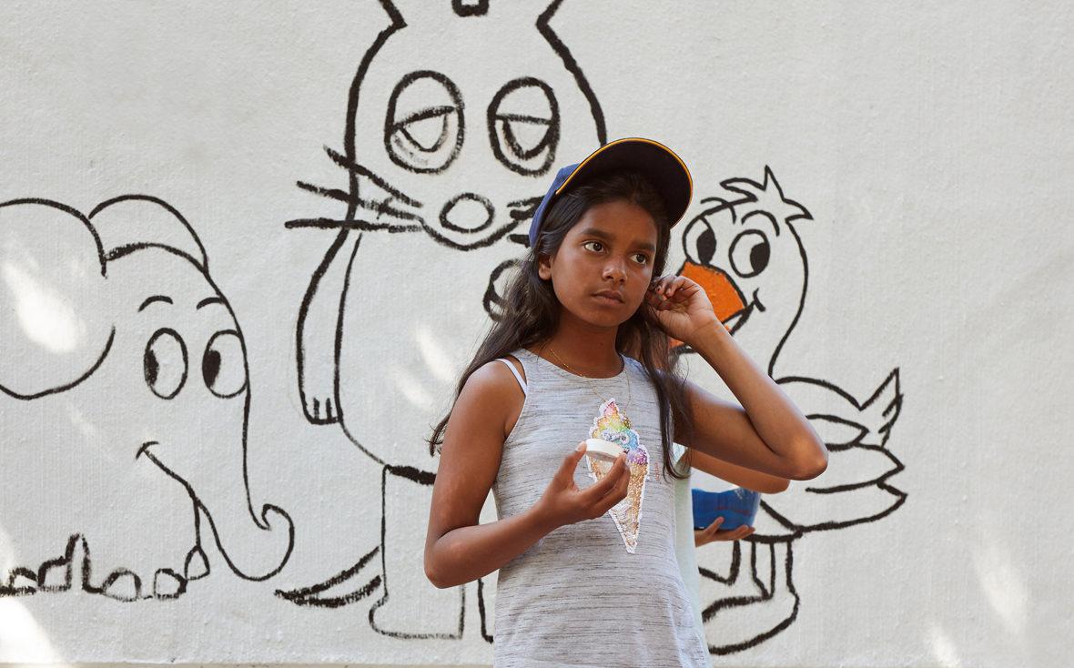 Mädchen steht vor weißer Wand, im Hintergrund sind die Umrisse von der Maus und dem Elefanten aus der ARD-Sendung zu sehen.