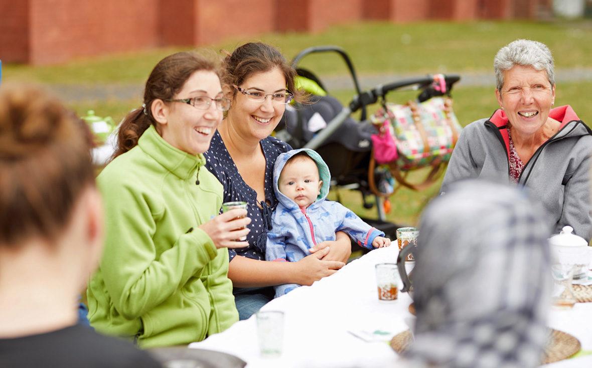 Mehrere Frauen und ein Baby am Tisch.