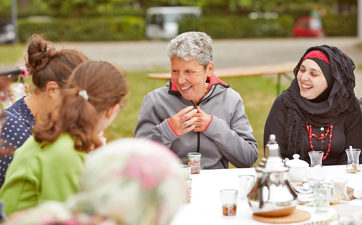 Frauen sitzen am Tisch und lachen.