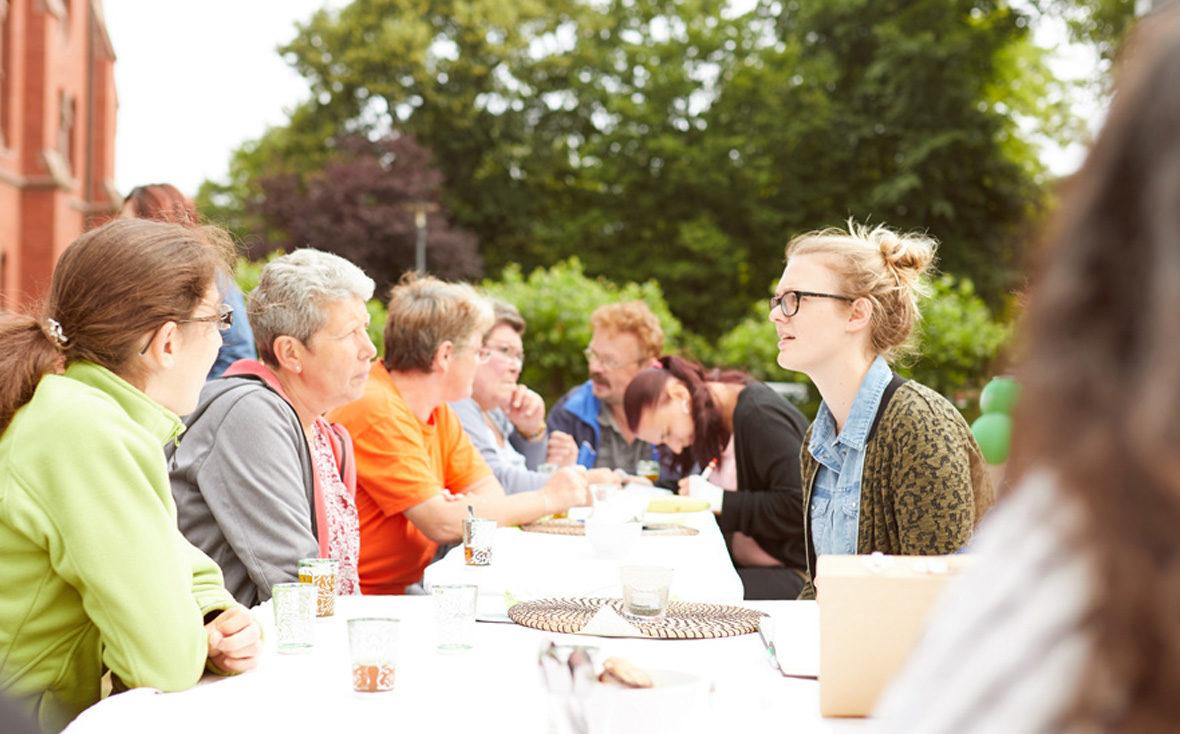 Alle sitzen gemeinsam an einer langen Tee-Tafel und unterhalten sich.