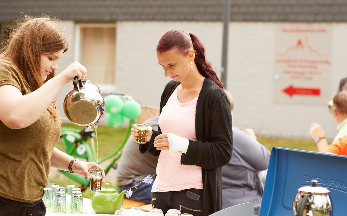 Eine Frau holt sich ein Gläschen Tee am Mobilitea-Stand.