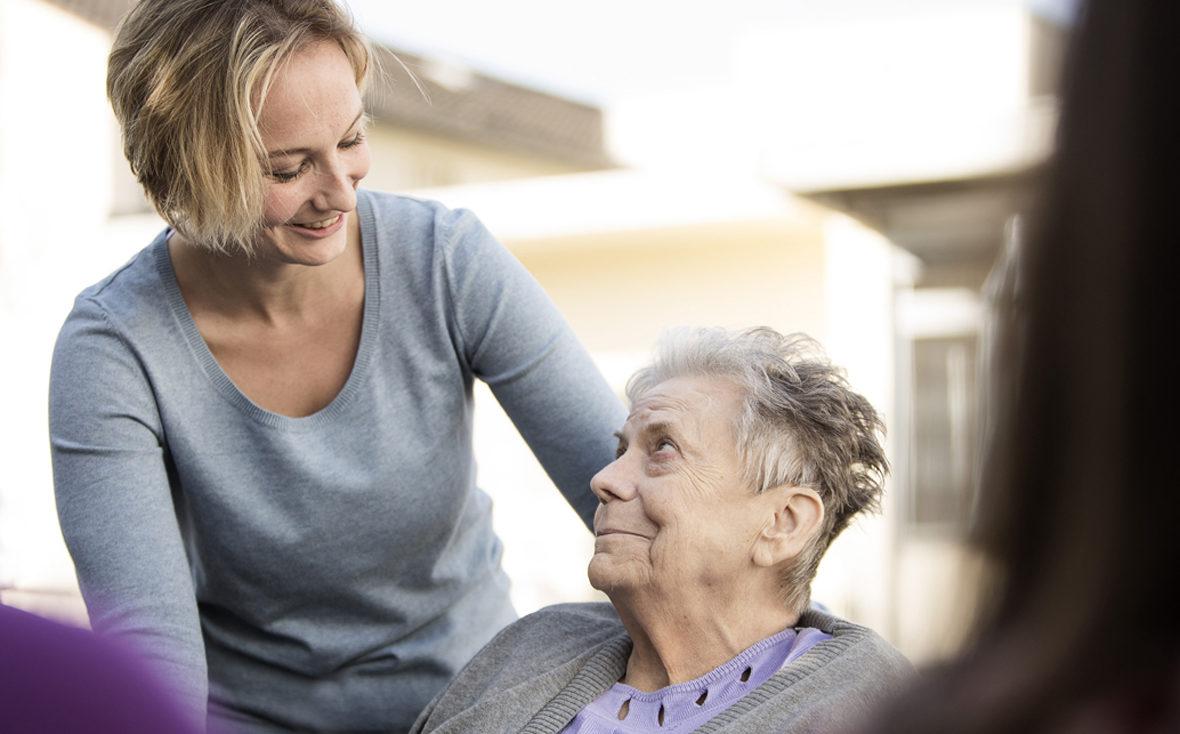 Eine jüngere Betreuerin schaut eine ältere, sitzende Dame freundlich an.